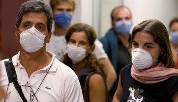 Argentine tourists wear surgical masks inside the airport in Mexico City May 3, 2009. The tourists are finally going home after Argentina cancelled flights to Mexico temporarily due to a flu outbreak. Mexico's flu epidemic has passed its peak, the Mexican government said on Sunday, and experts said the new H1N1 virus still could impact world health but may be no more severe than normal flu. REUTERS/Jorge Dan (MEXICO HEALTH TRANSPORT TRAVEL)