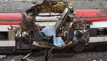 SPANISH POLICEMAN WALKS PAST WRECKAGE AFTER TRAIN EXPLOSION IN MADRID.