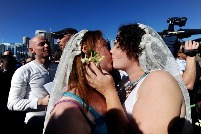 epa01812789 A same-sex couple kiss as they are illegally wed in a mass ceremony during a protest outside the Sydney Convention Centre where the 45th ALP National Conference is being held, in Sydney, Saturday, Aug. 1, 2009. The protest was part of a national day of action for same-sex marriage.  EPA/TRACEY NEARMY AUSTRALIA AND NEW ZEALAND OUT