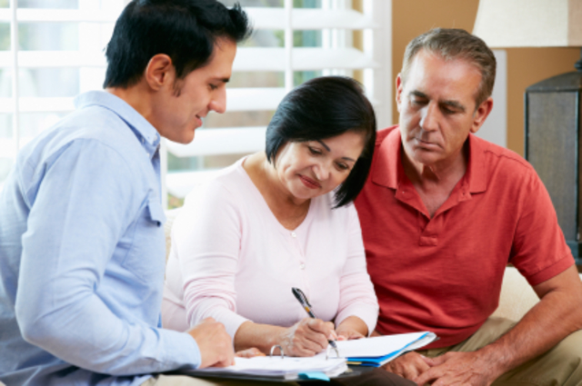 Financial Advisor Talking To Senior Couple At Home