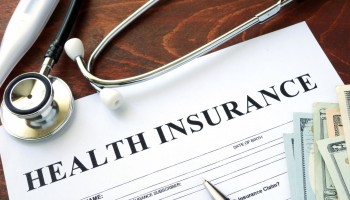 47220965 - health insurance  form and dollars on the table.